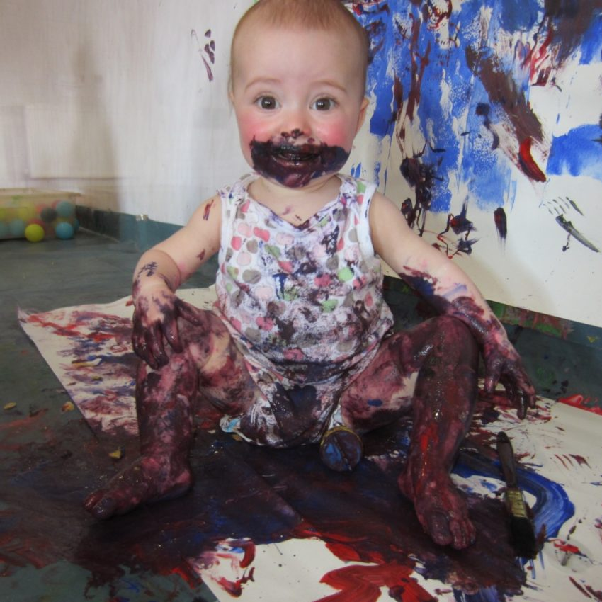 messy baby in paint